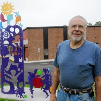 "ANDREW JANSEN / JOURNAL Don Horstman, a former art teacher in the Affton School District, stands next to ""Childhood"" at the Affton Early Childhood Center."
