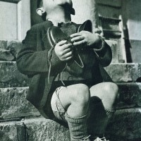 Image is from Life Magazine, 1946: It is a photo of an orphan with his first pair of new shoes.